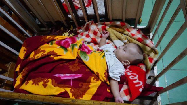 Một cậu bé 4, 5 tháng tuổi ngủ ngon trong cũi gỗ ở chùa Thiện Tâm